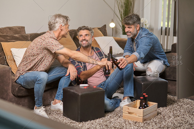 Full body of cheerful handsome men clinking with beer bottles spending weekend time together in bright cozy living room