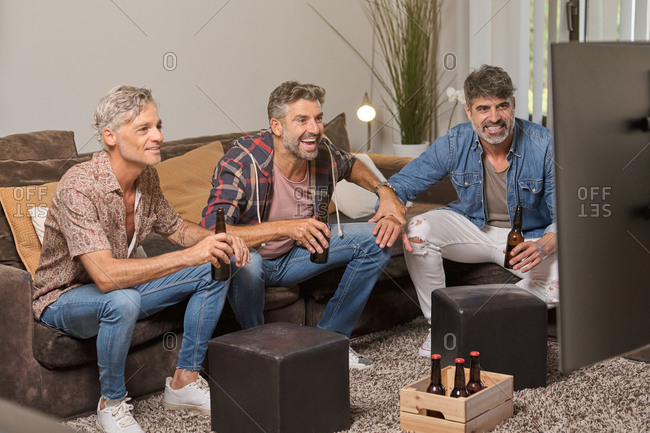 Happy mature men drinking beer and laughing while chilling on sofa and watching TV in cozy living room