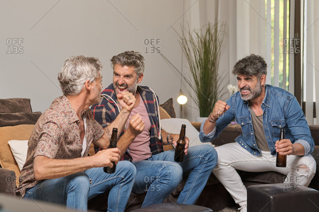 Happy mature men drinking beer and raising hands while celebrating success of sport team watching match in living room