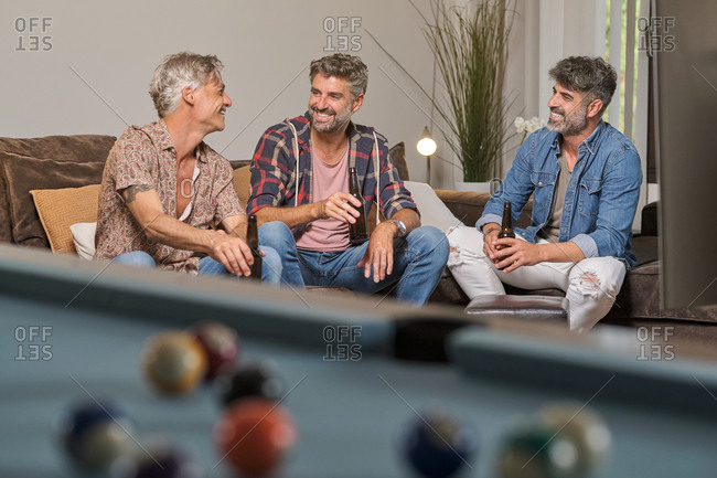 Full body of cheerful handsome men with beer bottles spending weekend time together in bright cozy living room