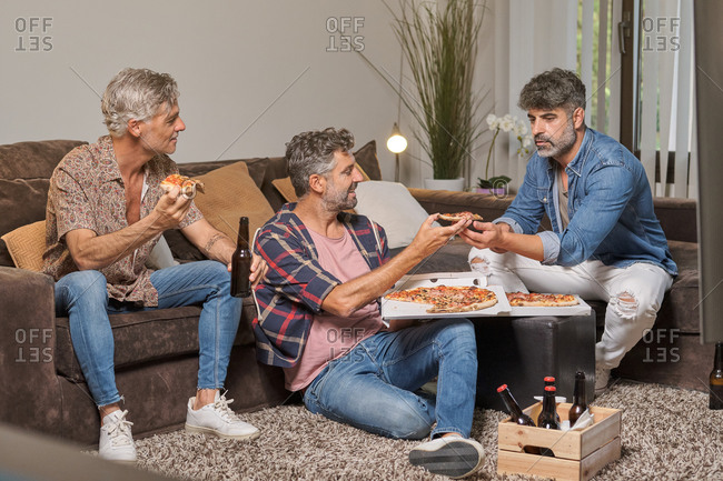 Full body of cheerful mature ethnic friends sharing pizza with beer bottles spending time together in cozy living room