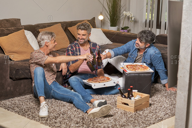 Full body of cheerful mature ethnic friends cheering with beer bottles and sharing pizza spending time together in cozy living room
