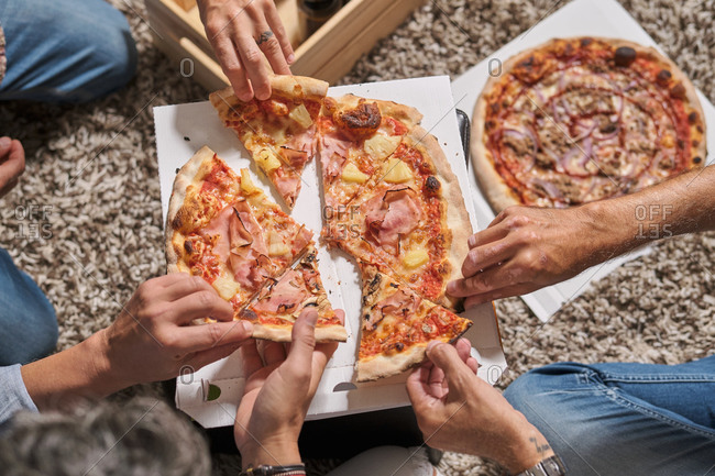Overhead view of cropped unrecognizable males enjoying delivered appetizing pizza while resting on carpet at home