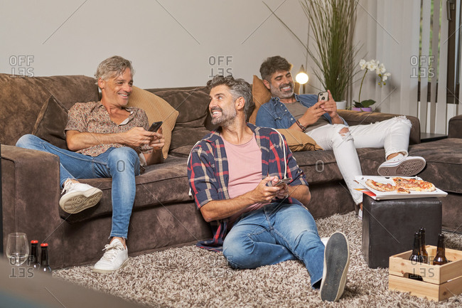 Full body of cheerful young ethnic men in casual clothing surfing internet with bright toothy smile while eating pizza and drinking beer in bright cozy living room