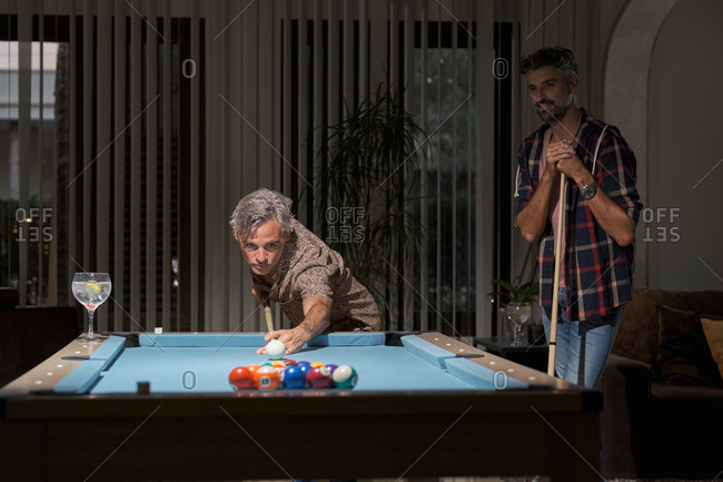 Happy mature friends in casual clothing playing pool and drinking cocktails while resting in cozy room in light of lamps