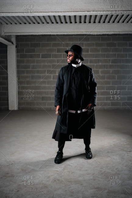 African American male in black clothes and stylish round sunglasses standing in underground garage and looking away