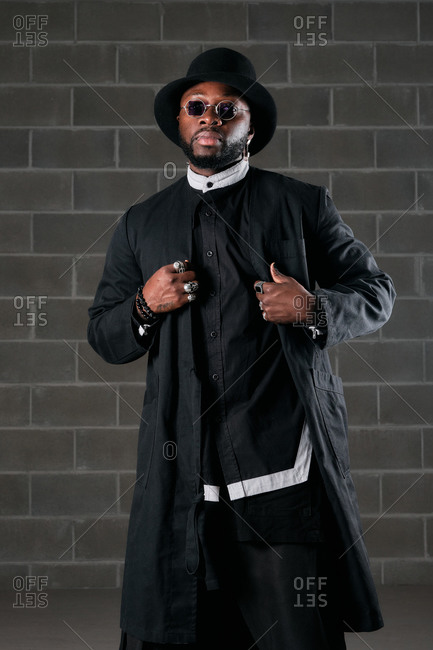 African American male in black clothes and stylish round sunglasses standing in underground garage and looking at camera