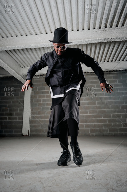 Low angle of African American male hip hop dancer in black apparel rehearsing in underground garage and showing choreography movements
