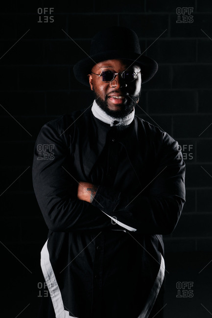 Happy African American male wearing round sunglasses and trendy black clothes standing on dark background in studio and looking at camera