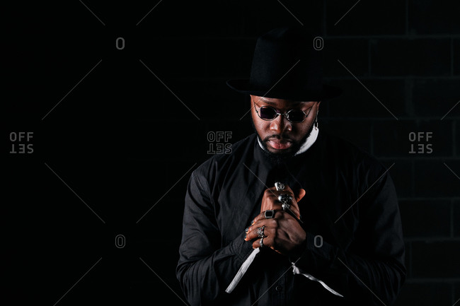 Determined African American male wearing round sunglasses and trendy black clothes standing on dark background in studio and looking down