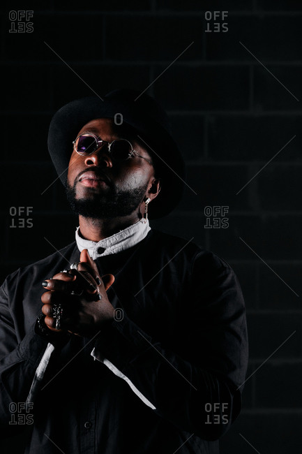 Determined African American male wearing round sunglasses and trendy black clothes standing on dark background in studio and looking at camera