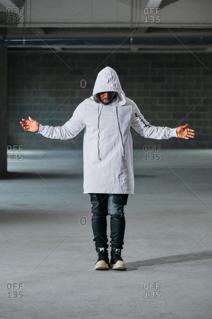 Full body of African American male in street style clothes and hood standing with outstretched arms in bright underground and looking down