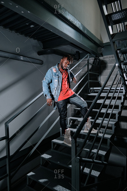 Low angle of thoughtful African American male in trendy apparel and with denim jacket standing on metal staircase and looking at camera