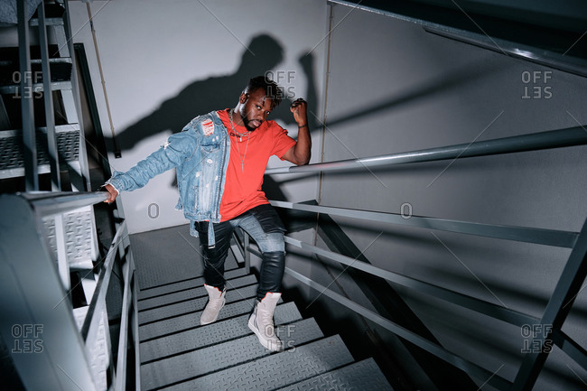 High angle of thoughtful African American male in trendy apparel and with denim jacket standing on metal staircase and looking at camera