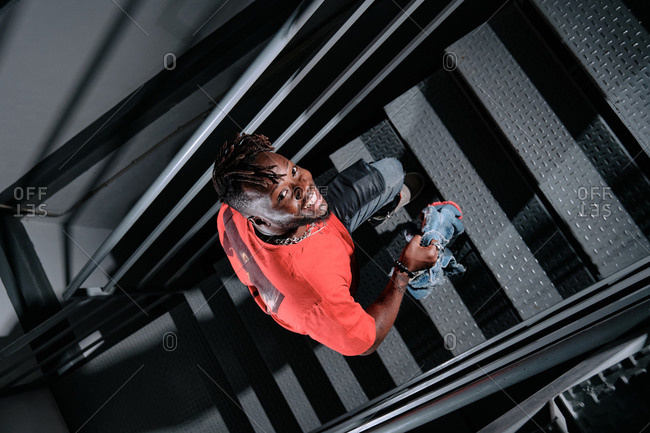 From above of positive African American male in stylish wear walking up metal stairs and looking at camera