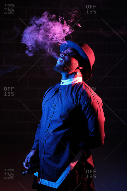 Side view of stylish African American male in hat and sunglasses standing on black background in studio with neon illumination and smoking vape while exhaling steam
