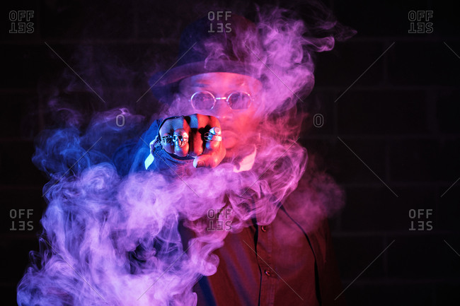 Stylish male showing fist with rings in shape of skull looking at camera in cloud of smoke illuminated by purple neon light in dark studio