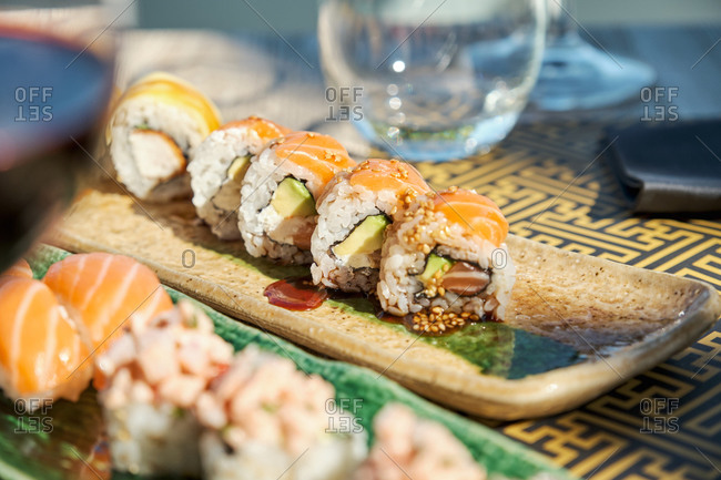 Sets of assorted sushi and rolls served on table in Asian restaurant