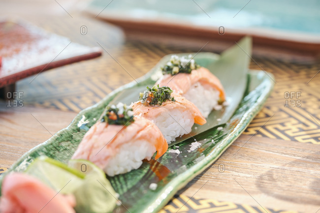 Closeup of delicious sushi Nigiri with salmon and greenery served on plate in Asian restaurant
