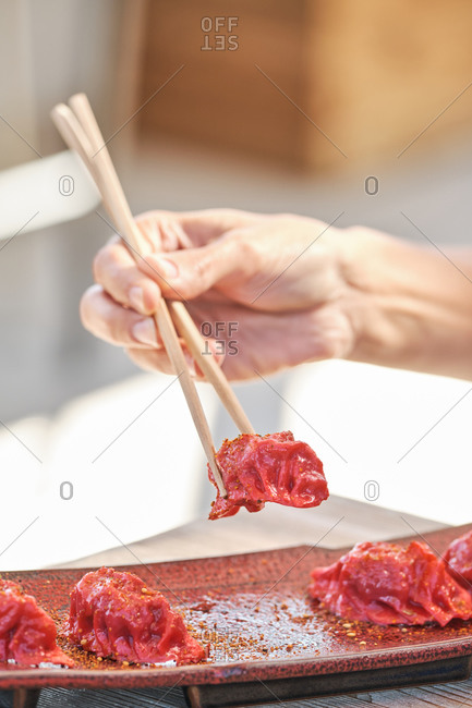 Cropped unrecognizable person hands holding chopstick eating delicious tuna sushi garnished with chili threads served on table in Asian restaurant