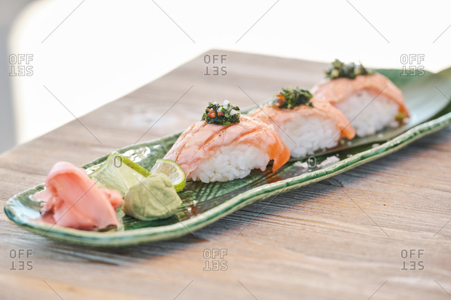 Delicious sushi Nigiri with salmon and greenery served on plate in Asian restaurant