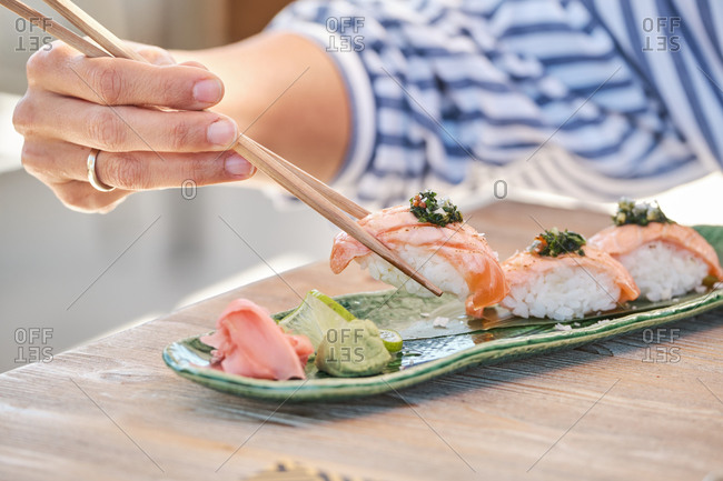 Cropped unrecognizable person hands holding chopstick eating delicious sushi Nigiri with salmon and greenery served on plate in Asian restaurant