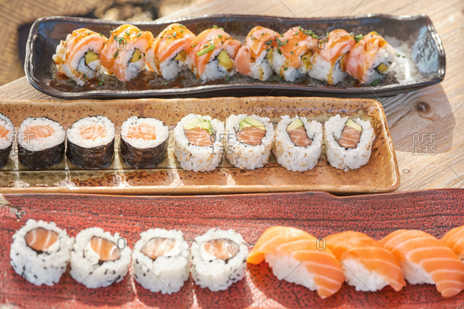 High angle of sets of assorted sushi and rolls served on table in Asian restaurant