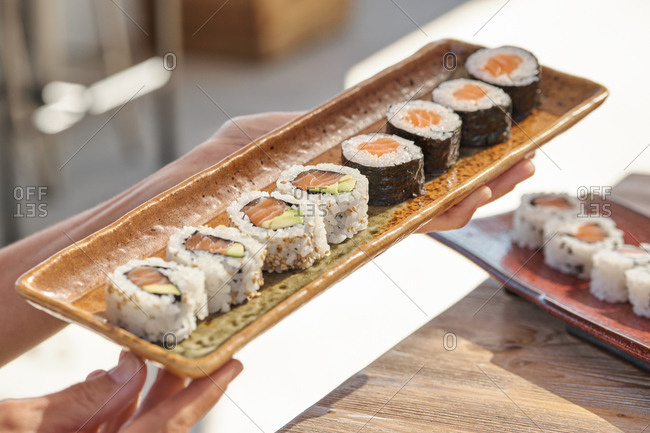 High angle of sets of assorted sushi rolls served on table in Asian restaurant