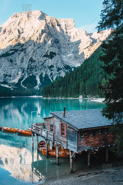 Majestic scenery of wooden house located on shore of clear lake with turquoise water and boats floating on smooth surface on background of mountains in morning light