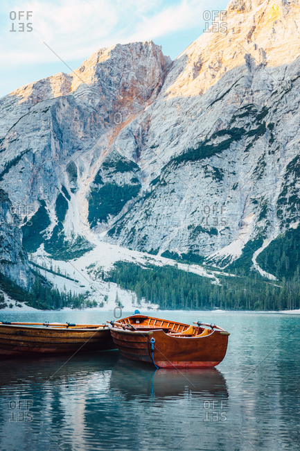 Wooden boat floating on turquoise water of calm lake on background of majestic landscape of highlands
