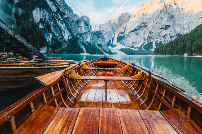 Wooden boat with paddles floating on turquoise water of calm lake on background of majestic landscape of highlands