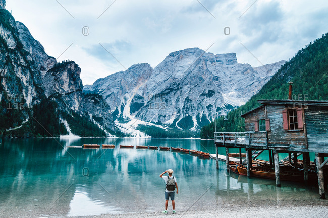 Back view of anonymous male explorer with backpack standing on shore of crystal clear lake with turquoise water and enjoying scenery of mountains during vacation