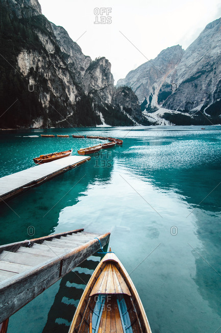 From above wooden quay on amazing scenery of lake with turquoise water in mountains on foggy day