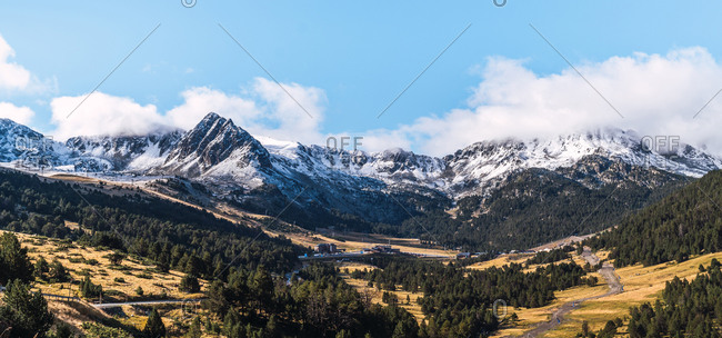 Picturesque panoramic landscape of green valley with coniferous forest against majestic snow covered peaks of Pyrenees mountains under blue cloudy sky in sunny day in El Pas de la Casa in Andorra