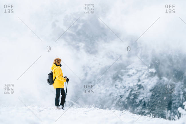 Side view of anonymous hiker with trekking poles walking on snowy ground in Pyrenees mountains in Andorra