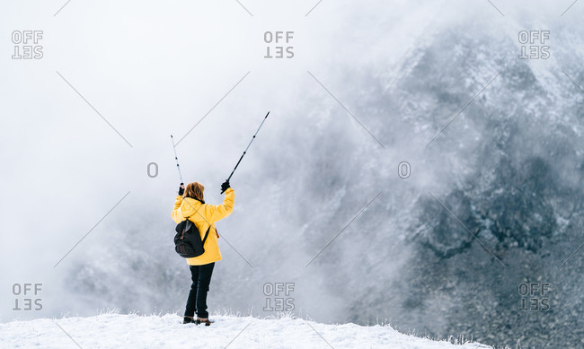 Full body back view of unrecognizable female hiker with backpack and trekking sticks standing on top of snowy mountain ridge in cold winter weather with snowfall while travelling through Pyrenees mountains
