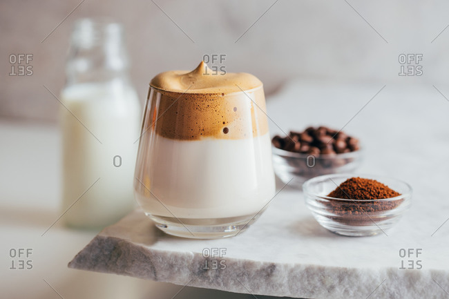 Aromatic Dalgona beverage in glass placed on edge of marble table with instant coffee and beans
