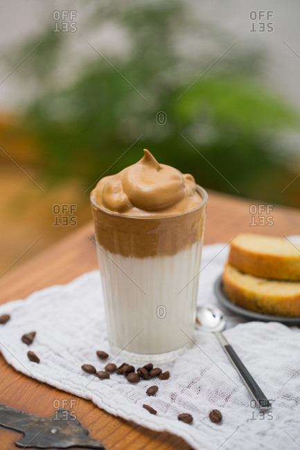 Glass of tasty Dalgona beverage with whipped instant coffee and milk placed on table in cafe with cake for breakfast