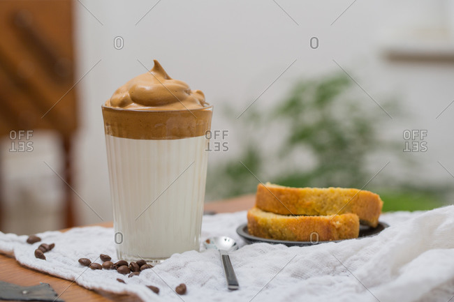 Glass of tasty Dalgona beverage with whipped instant coffee and milk placed on table in cafe for breakfast with cake