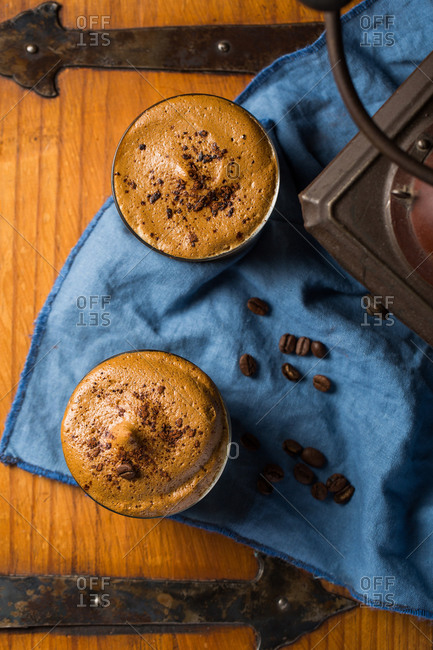 Top view of delicious Dalgona beverage with foam garnished with chocolate and placed on table with coffee grains and napkin in cozy cafe