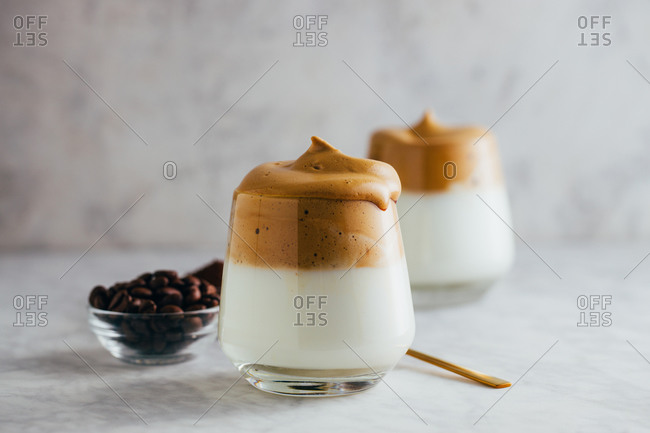 Aromatic Dalgona beverage in glass placed on marble table with instant coffee and beans