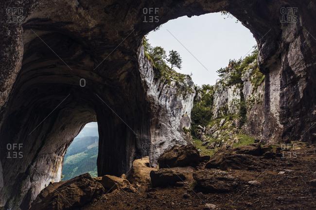 Picturesque view of bristly cave and mounts near growing trees in Basque Country