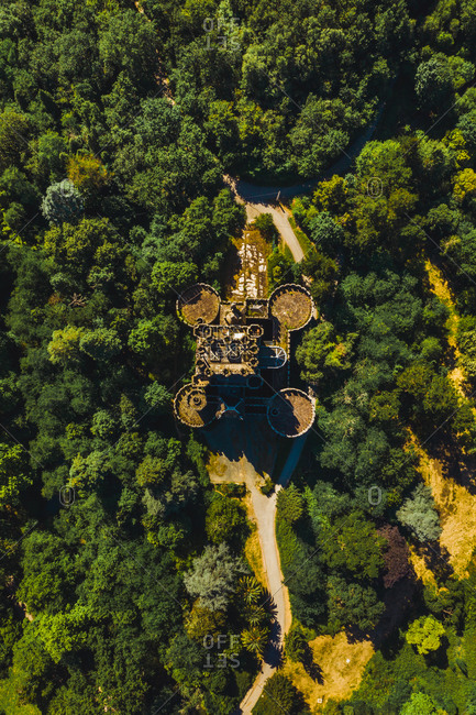 Aerial view of aged stone building surrounded by lush green woods near narrow pathway in Basque Country