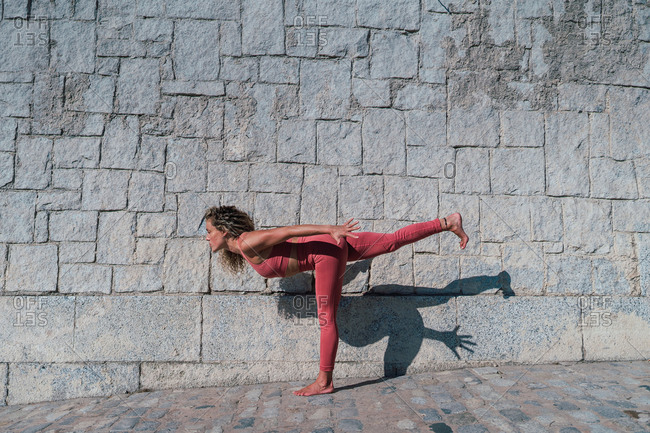 Full body side view of focused barefoot female in pink sportswear doing variation of Warrior pose with airplane arms against old stone wall