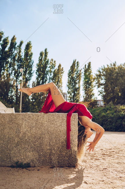 Full body side view of sensual slim female in red dress lying on stone fence with legs raised while stretching body in yoga position