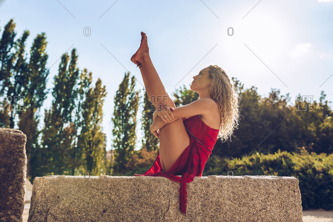 Full body side view of flexible female sitting on stone border and stretching in Boat with Thighs to Chest pose while practicing yoga in summer park