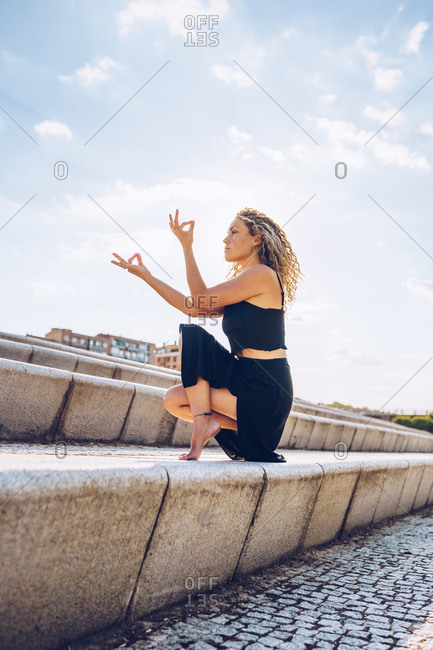 Full body side view of concentrated female in black sportswear doing Toe Stand and keeping hands with mudra gesture while practicing yoga and meditating on stone stairs