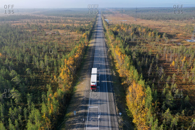 Drone view of picturesque curved roadway leading through valley with colorful trees in autumn