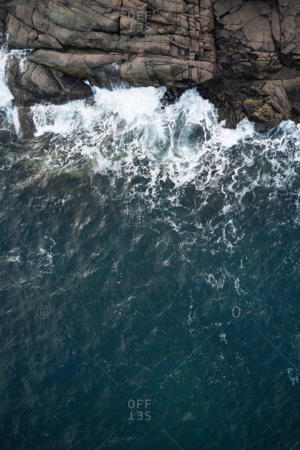 Drone view of foamy blue sea waving on rocky shoreline with rough boulders