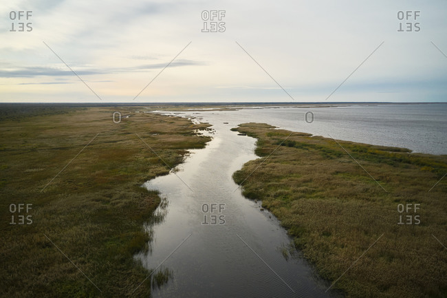 Wonderful drone view of calm river flowing into sea under peaceful sunset sky
